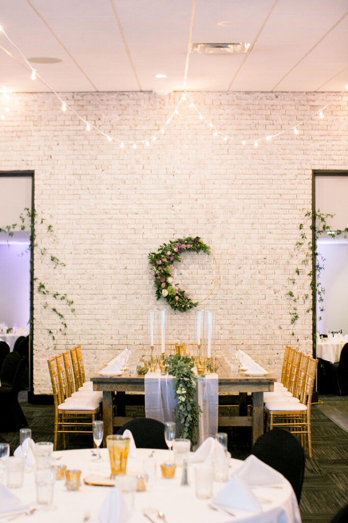 Decorated wooden table and chairs in front of a white brick wall at a wedding reception.
