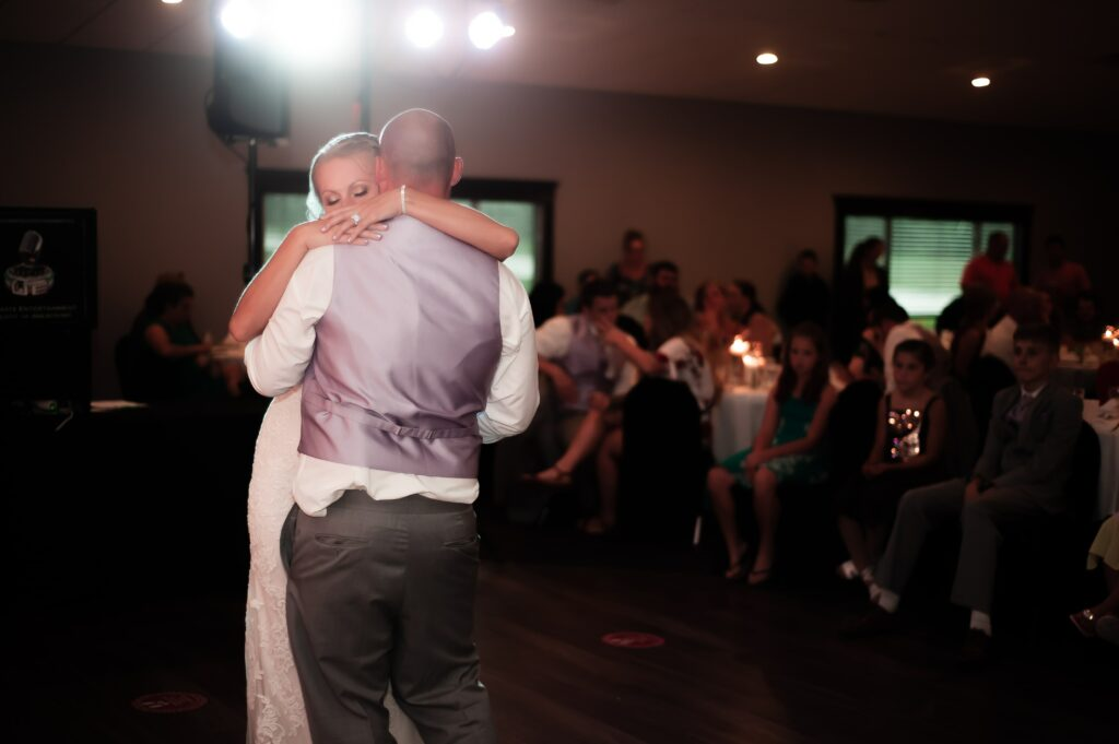 Husband and wife dancing their first dance in front of wedding guests.