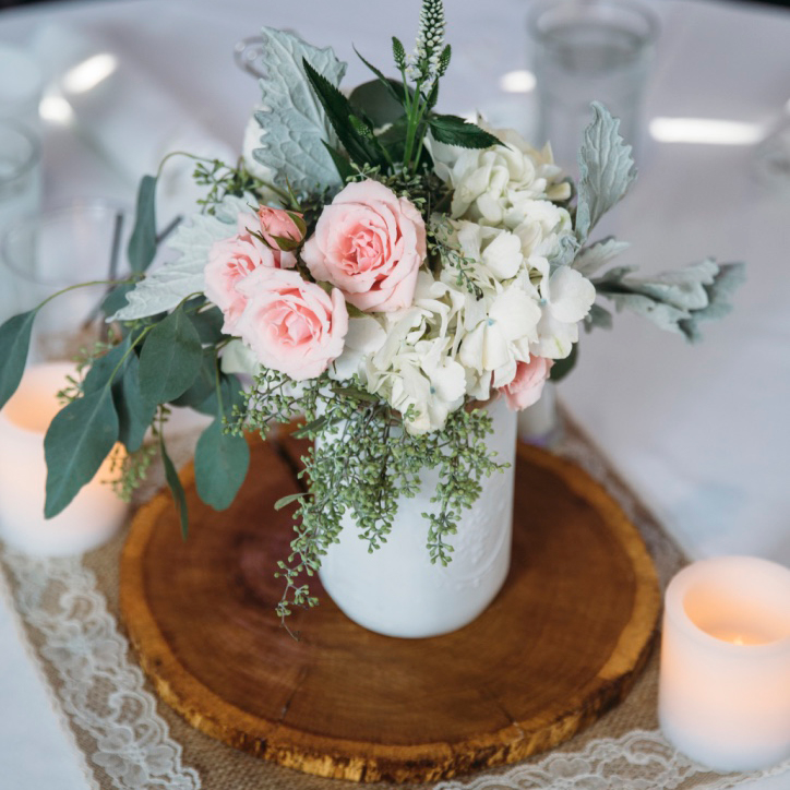 Centerpiece composed of wooden slab with white mason jar full of flowers on top and candles around it.