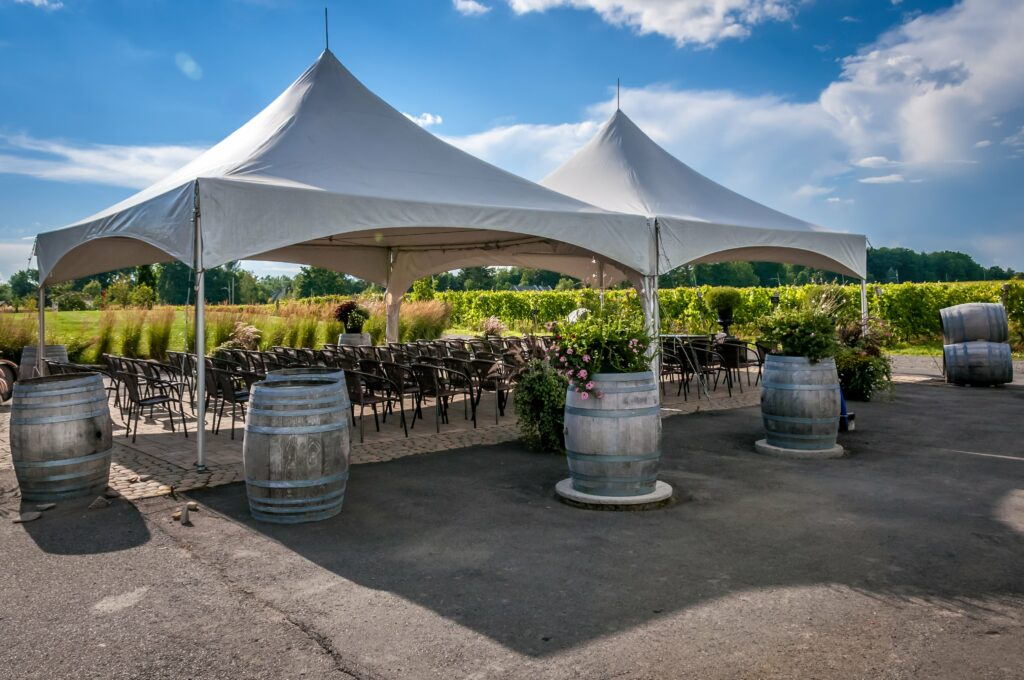 Outdoor wedding ceremony set up under canopy tents with wine barrels placed around the tents.