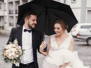Bride holding up dress while walking in the rain with groom under an umbrella.