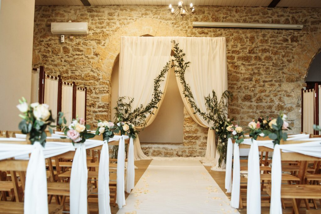 Indoor wedding ceremony setup with alter and rows of chairs.