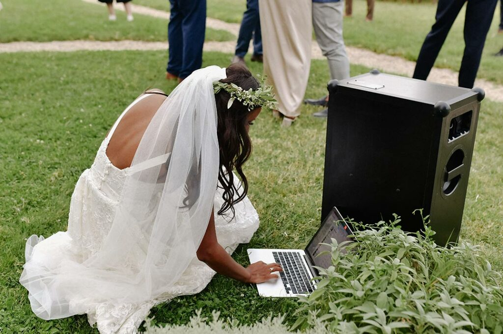 Bride bending dow to start music on a laptop for an outdoor reception.
