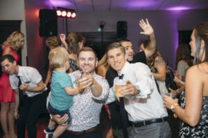 Two men dancing at wedding, smiling and pointing at the camera while one man holds a toddler.