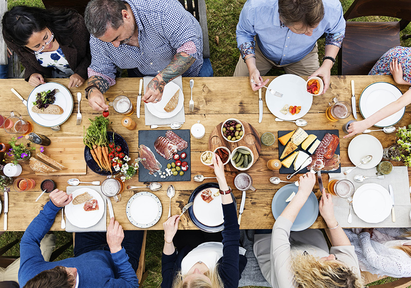 Group gathered at a picnic table sharing a meal together.