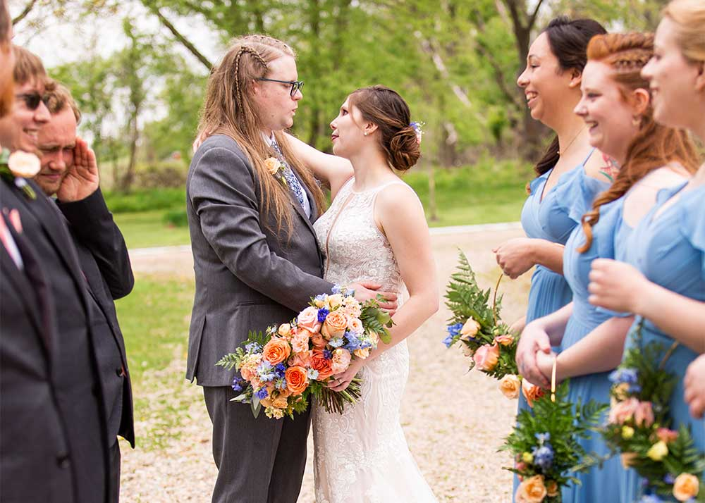 """Bride and groom making funny faces at each other while standing at the end of a """"tunnel"""" formed by the wedding party."""
