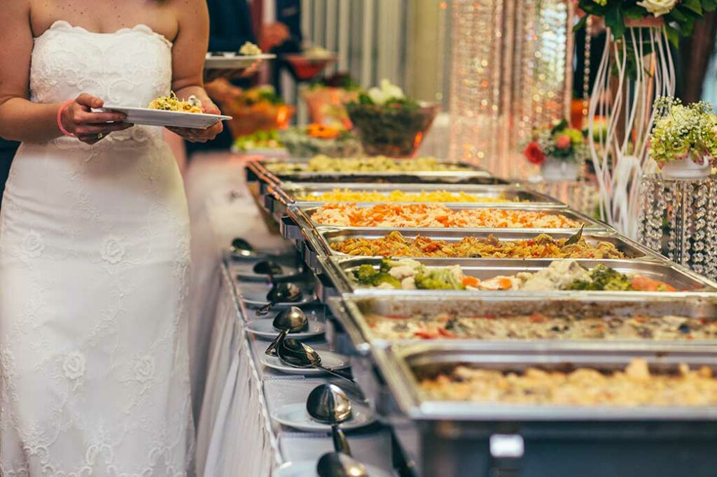 Bride walking down buffet line while holding a plate.