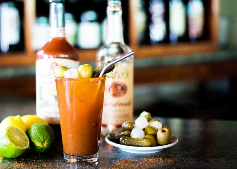 Bloody Mary drink sitting on a bar top with toppings next to it.