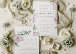 Wedding invitations with flowers and ribbons around them.